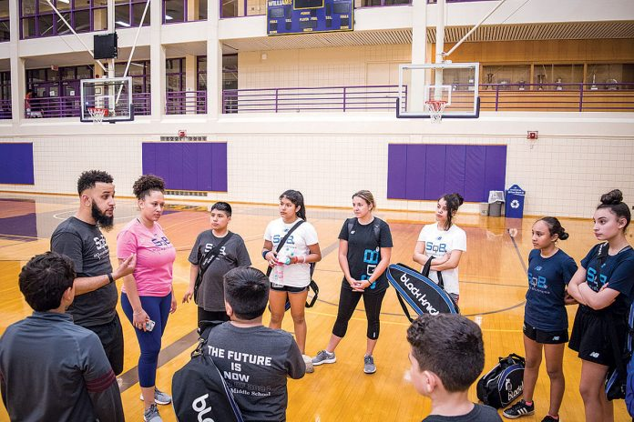 GIVING BACK: Rodney Galvao, left, program director of SquashBusters Providence, and Vania Pereira, center, alumna and volunteer, gather with SquashBusters players during the Urban Individual Nationals competition at Williams College in Williamstown, Mass., in June. / COURTESY SQUASHBUSTERS PROVIDENCE
