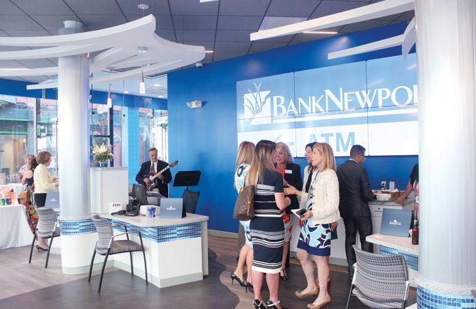 OPEN FOR BUSINESS: Guests mingle and converse at the new BankNewport branch on Dorrance Street in Providence during the open house event June 26 celebrating the branch's grand opening. The branch replaced the former AAA branch with a full redesign, replacing the teller counter with pod stations for customer seating, making the space more open. The full-service branch also includes two indoor personal teller machines. / After photos: PBN PHOTOS/JAMES BESSETTE