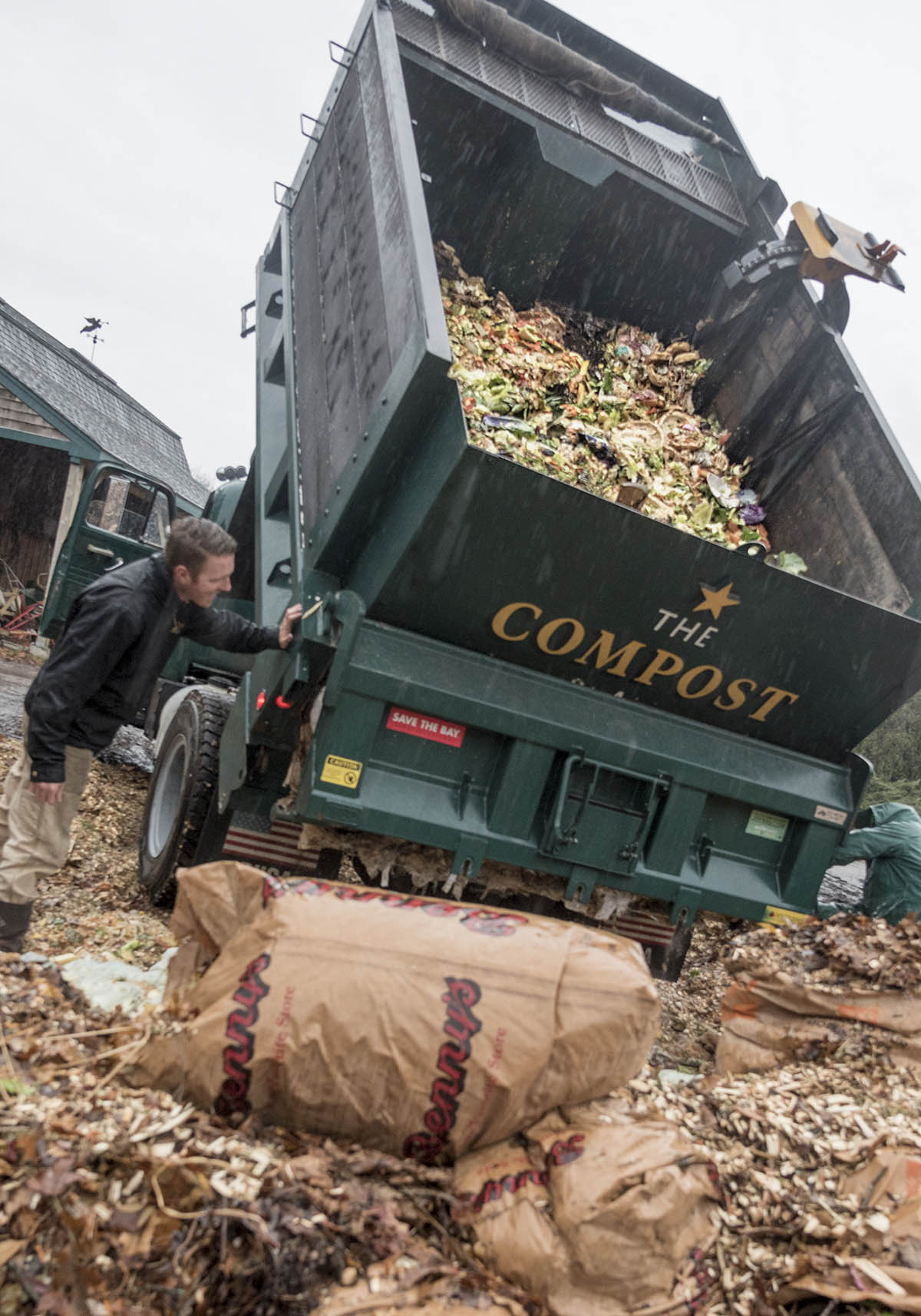 FOOD SCRAPS: Leo Pollock of The Compost Plant, left, and employee Monica Shinn, who does collections and welding on the vehicles for The Compost Plant, dump food scraps at Earth Care Farm in Charlestown, the state's largest composting facility in which food-waste producers can bring their material. / PBN FILE PHOTO/MICHAEL SALERNO