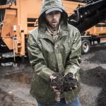 FINISHED PRODUCT: Sam Fox, a former assistant manager at Earth Care Farm in Charlestown, shows a handful of finished compost. The farm is the state's largest facility at which commercial-scale food-waste producers can divert materials to keep them out of the Central Landfill in Johnston.
