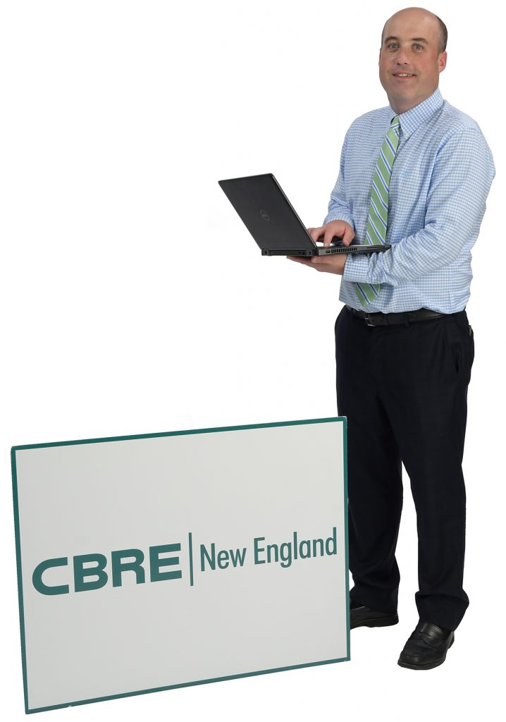 "the prop: Andrew Galvin's laptop and a CBRE sign say it all. ""It's an unbelievable company. … I'm really excited about the future."" / PBN PHOTO/MIKE SKORSKI"
