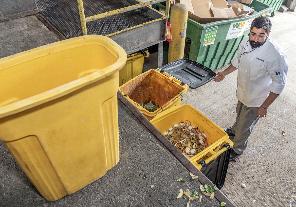 DESIGNATED BINS: Hemenway's chef Jerome Romanofsky dumps the food waste into the yellow compost-only bins at the loading dock in back of the restaurant. / PBN PHOTO/MICHAEL SALERNO