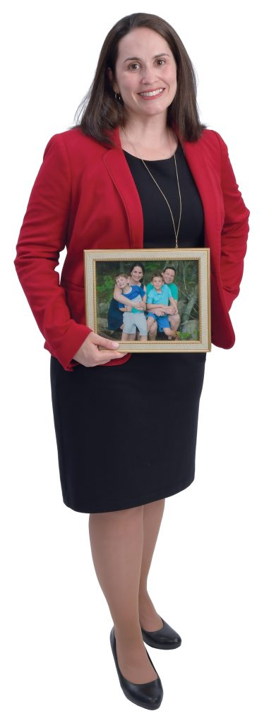 "the prop: Bridget Mullaney holds a photo of her family: husband, James Nagelberg, and sons Benjamin, 4, (left) and Jack, 7. ""They're both characters, in their own ways,"" she said about the boys. / PBN PHOTO/MIKE SKORSKI"