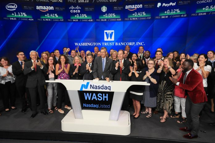 A GROUP OF EMPLOYEES from Westerly-based Washington Trust Bancorp, led by Chairman and CEO Edward O. Handy III (center), ring the opening bell Tuesday for the Nasdaq Stock Market in New York. / COURTESY NASDAQ AND WASHINGTON TRUST