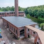 TAKE THEM TO THE RIVER: Pontiac Mills in Warwick is a sprawling former Fruit of the Loom mill complex across from Warwick Mall that is being redeveloped along the Pawtuxet River into residential and commercial space. / PBN PHOTO/MICHAEL SALERNO