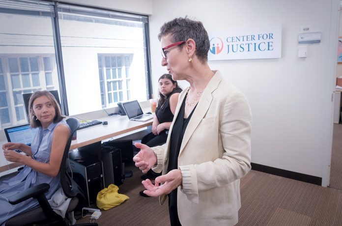 MAKING A DIFFERENCE: Jennifer Wood, foreground, executive director of the Rhode Island Center for Justice, helps provide legal access for those who either cannot afford it or don't know they qualify for it. Helping out are interns Sydney Anderson, left, and Tallia Akay. 