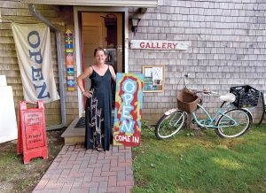 ART SUPPORTER: Paige Gaffett stands in front of the Block Island nonprofit artist cooperative Spring Street Gallery, where she serves as a coordinator. Gaffett previously co-founded the HeART Space Community Art Center on Block Island with Felicia Cinquegrana in February 2015 as a place for art classes, gallery shows and a retail outlet for local artisans but had to close in January 2017 due to high rents and not generating enough income to be sustainable year-round. / PBN PHOTO/MALCOLM GREENAWAY