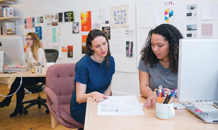 DESIGN TEAM: Sarah Rainwater, center, founder, president and creative director of Studio Rainwater, talks with designer Danikqwa Rambert, right, at the firm's office in East Providence. Art Director Sarah Verity works in the background.