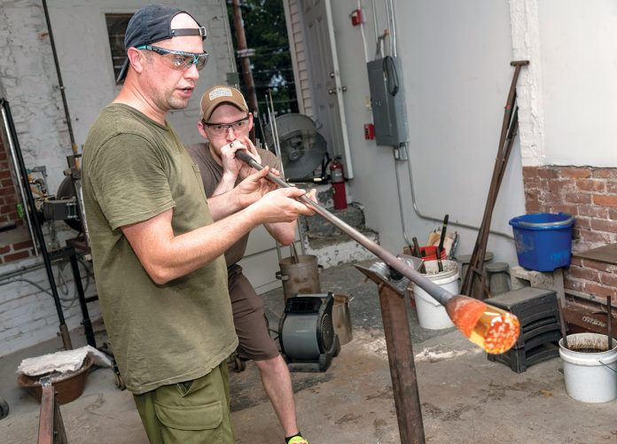 PASSING IT ON: Ben Giguere, left, founder of Gather LLC, on Atwells Avenue in Providence, shows Jairus Burdick how to make a drinking glass. / PBN PHOTO/MICHAEL SALERNO