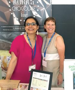 MAKING CONNECTIONS: Aura Fajardo, left, owner and chocolatier at Aura's Chocolate Bar, and Ginny McQueen of Shady Lane Granola attend a tabletop trade show held at the Hope & Main culinary incubator in Warren April 26. / COURTESY R.I. COMMERCE CORP.