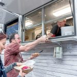 LICENSE TO SELL: Adam Batchelder, right, owns food truck Smoke & Squeal BBQ. He serves Elena and Bob Given, of Mansfield, biscuits, pickled watermelon rind, and mac and cheese. Batchelder says he'll welcome the chance to get a single statewide license next year. / PBN FILE PHOTO/MICHAEL SALERNO