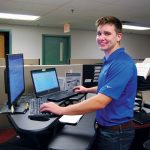 TAKING A STAND: Parkinson Technologies offers many initiatives to encourage a healthy lifestyle among its workers, including access to standing desks. Taylor Fortier, sales applications engineer, works at his standing desk in the company's Woonsocket office.  / COURTESY PARKINSON TECHNOLOGIES INC.