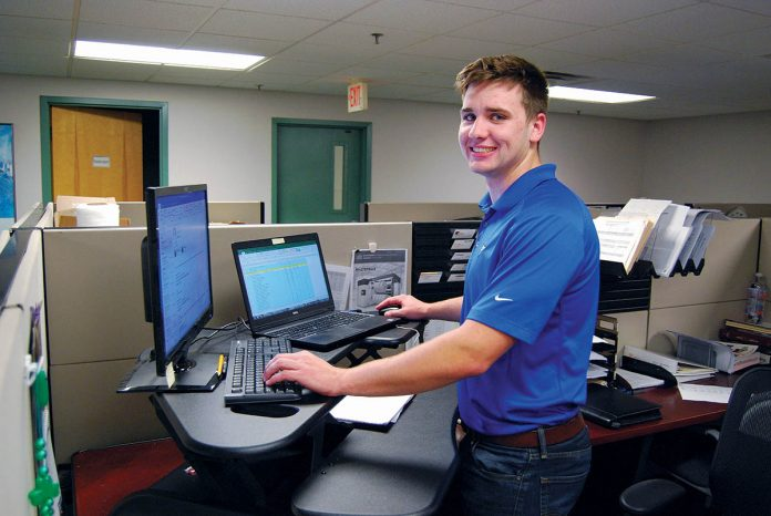 TAKING A STAND: Parkinson Technologies offers many initiatives to encourage a healthy lifestyle among its workers, including access to standing desks. Taylor Fortier, sales applications engineer, works at his standing desk in the company's Woonsocket office. 