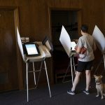 IN A RECENTLY RELEASED CBS NEWS POLL, nearly two-thirds of U.S. voters rated the economy as either very good or somewhat good. Here a voter casts a ballot with her dog at a polling location in Utah. / BLOOMBERG NEWS FILE PHOTO/KIM RAFF
