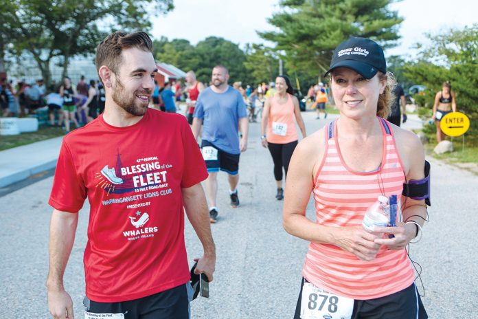 WELLNESS WARRRIORS: Kenny Boucher, left, a supervisor in the CBIZ audit department, and Danielle Poyant, director in the tax department, both members of the 15-person Road Warriors, runners from the Boston and Providence offices, compete in the Blessing of the Fleet 10-mile race in Narragansett July 27.  / PBN PHOTO/RUPERT WHITELEY