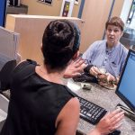 CASH BONUS: The Washington Trust Co. said it was able to provide employees with one-time cash bonuses in January as a result of a reduction in its corporate taxes. Patricia Fernandez, left, professional flex banker at Washington Trust on Waterman Street in Providence, speaks with customer Nina Pratt of Providence.