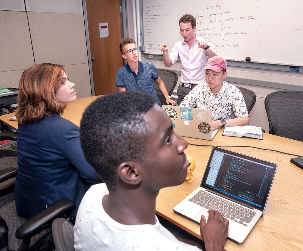 INNOVATIVE STAFF: Providence technology company Pangea.app is developing a platform to connect college students to the gig economy. Co-founder and CEO Adam Alpert, standing, speaks with his colleagues, from left in foreground, Rachel Gross, head of user success, and Chinenye Uduji, software engineer, and in background, Andrew Thompson, left, head of branding, and Francis Park, UI/UX designer.