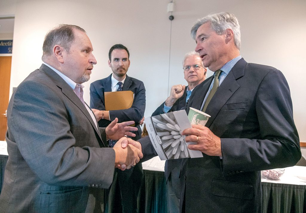 ENERGIZED MEETING: Enhanced Energy Group President Paul Dunn, left, shakes hands with Sen. Sheldon Whitehouse during the senator's ninth annual Energy, Environment and Oceans Leaders Day at the R.I. Convention Center in Providence. Looking on in the background are Aaron Goldner, left, energy and transportation policy adviser for Whitehouse, and Rick Mobley, business development, Enhanced Energy Group. / PBN PHOTO/MICHAEL SALERNO