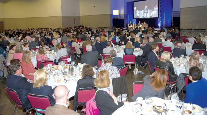 ECONOMIC ENGAGEMENT: Attendees listen to Gov. Gina M. Raimondo speak during an economic-outlook luncheon event in 2017 at the R.I. Convention Center. The Greater Providence Chamber of Commerce's latest luncheon, to be held Sept. 24, will feature Ravi Kumar, president and deputy chief operating officer for Infosys.