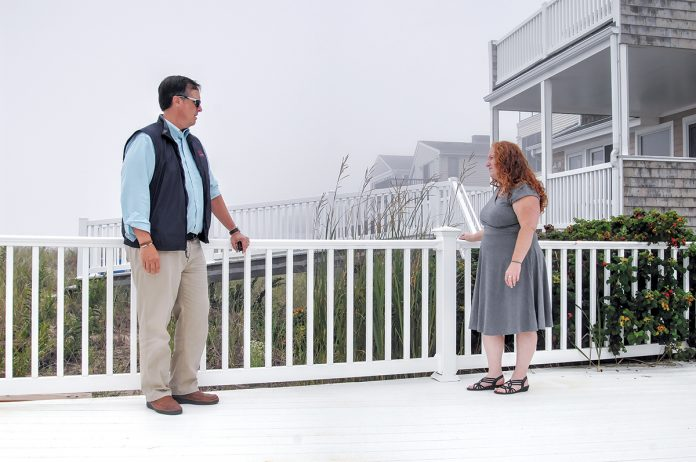 RIGHT FIT: Sarah Lassor and Howard Thorp, of Thorp & Trainer Insurance, are on a deck on Atlantic Avenue in the Misquamicut section of Westerly. Thorp says private flood insurance isn't right for ­everyone.