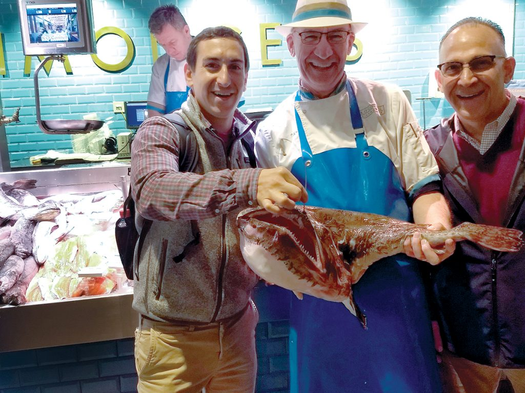 PROMOTING PROVIDENCE: Gracie's executive chef Matthew Varga, left, and Siena Restaurant Group executive chef Anthony Tarro, right, talk seafood with Pat O'Connell, a fishmonger in County Cork, Ireland. The chefs were part of a delegation that traveled to Ireland to promote Providence at the annual A Taste of West Cork culinary festival. / COURTESY GOPROVIDENCE/KATHLEEN CESERETTI