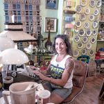 NOSTALGIA SELLS: Jennifer Ricci, co-owner of Providence-based vintage store Rocket to Mars, sits at a 1960s Royal typewriter, with a 1950s Moss Lighting Co. tall lamp. / PBN PHOTO/MICHAEL SALERNO