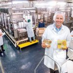 HOT STUFF: Blount Fine Foods President and CEO Todd Blount, with a couple of the company's new products, on its Fall River production line, from left, Beef PHO and Coconut Chicken & Noodle soups. / PBN PHOTO/DAVE HANSEN