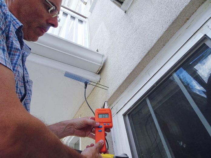 SEAL APPROVAL: Michael Kenney, co-founder and president of Building Enclosure Science, tests the front wall of a condominium complex in Chelsea, Mass., to see if there is moisture inside the walls, part of a test to make sure the building is keeping out the rain. / COURTESY BUILDING ENCLOSURE SCIENCE
