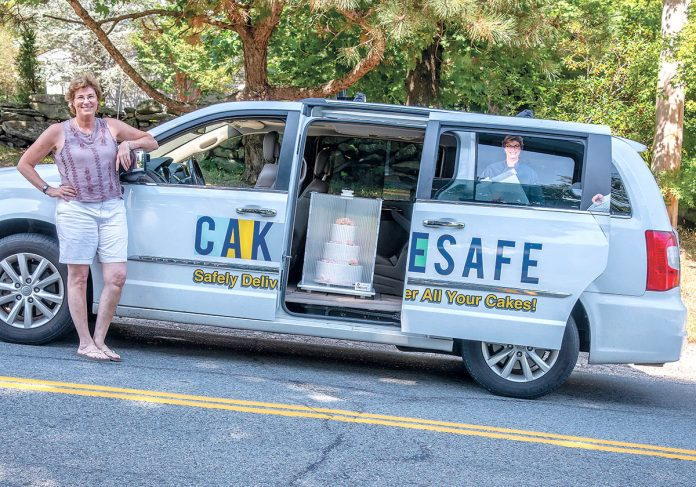 CAKE WALK: Juli Chapin, co-owner of CakeSafe, which produces a transportation system for safely moving cakes. Chapin is pictured on Torrey Road in South Kingstown, one of the town's steepest hills, using a CakeSafe to keep a cake in check on the steep incline.