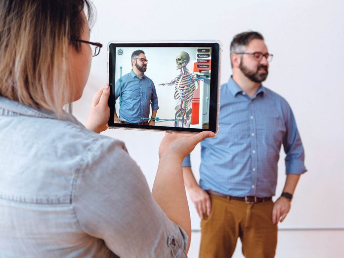 TECH TAUGHT: CrossTrainer Creative Services Manager Tiffany Yee demonstrates an augmented-reality training session, showing a life-sized skeleton alongside company founder Brian Boyle in an augmented-reality environment.  / PBN PHOTO/RUPERT WHITELEY