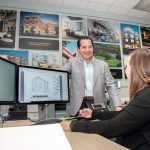 DEDICATED DESIGN: Eric Zuena, managing principal at ZDS, speaks with Julie Jancewicz Bartlett, project manager/associate. The wall behind Zuena features designs from many of the company's clients. / PBN PHOTO/MIKE SALERNO