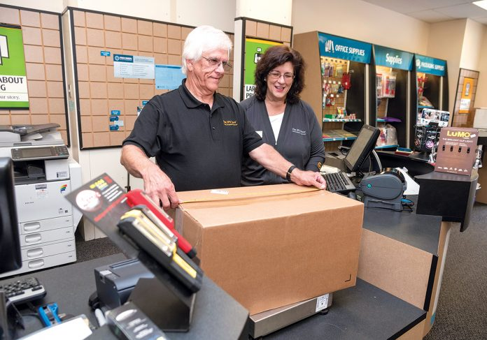 CAREER CHANGE: Aurelia Donovan, co-owner of the UPS Store on Mendon Road in Cumberland, at the counter with Thomas Nicholson, associate. Donovan opened the store with members of her family after working in the banking industry for several years. / PBN PHOTO/MICHAEL SALERNO
