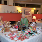A WOMAN OBSERVES items for sale during last year's Harvest Time Fair, hosted by United Methodist Elder Care, which has since become Aldersbridge Communities. This year's fair will be held Nov. 9-10 at two East Providence locations, Winslow Gardens and Linn Health & Rehabilitation. / COURTESY ALDERSBRIDGE COMMUNITIES