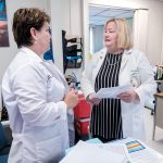 INFECTION PREVENTION: Lee Ann Quinn, right, director of infection prevention and control for South County Hospital in South Kingstown, speaks with Kristen Whelan, infection prevention, employee health analyst and flu clinic coordinator.