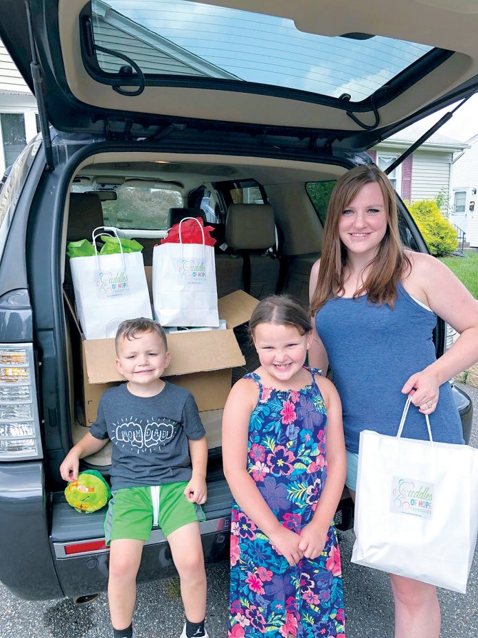 EXTRA COMFORT: North Providence resident Amy Antone, shown with her children, started the nonprofit Cuddles of Hope Foundation this past summer to donate gift bags to ailing children. / COURTESY AMY ANTONE