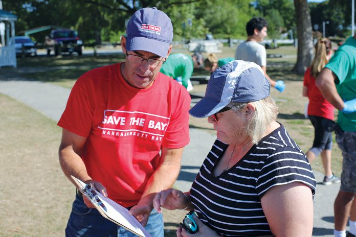 BEACH CLEANUP: Save The Bay Executive Director Jonathan Stone, left, speaks with a volunteer at a cleanup in the Oakland Beach neighborhood of Warwick during last year's International Coastal Cleanup Day. Above right, a logo in support of Question No. 3 on next month's ballot created by Save The Bay. 