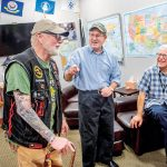 TELLING STORIES: Veterans, from left, Daniel Thurston, Dave Minto and Dan Evangelista talk in the Rhode Island Military Organization lounge at T.F. Green Airport in Warwick. The men were on hand in honor of Vietnam War pilot Lt. Col. Fredric Moore Mellor, shot down over the jungles of North Vietnam, whose remains were brought home last month. / PBN PHOTO/DAVE HANSEN