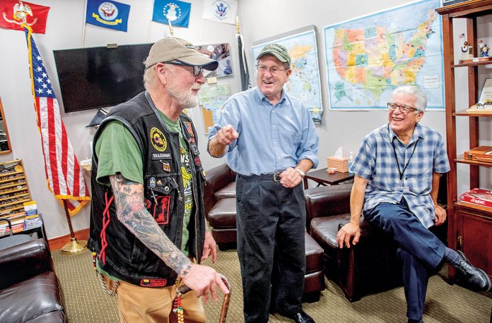 TELLING STORIES: Veterans, from left, Daniel Thurston, Dave Minto and Dan Evangelista talk in the Rhode Island Military Organization lounge at T.F. Green Airport in Warwick. The men were on hand in honor of Vietnam War pilot Lt. Col. Fredric Moore Mellor, shot down over the jungles of North Vietnam, whose remains were brought home last month.