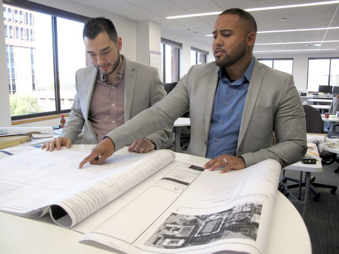 CAREER PATH: Christopher L. Calderon, left, and Edwin A. Montas, project engineers at Gilbane Building Co., benefited from an early introduction to construction. Calderon, who remembers being treated to pizza parties with elementary school classmates at the company's corporate office as recognition for good grades, said giving young people a chance to look beyond the careers of their parents is important.  / PBN PHOTO/MARK S. MURPHY