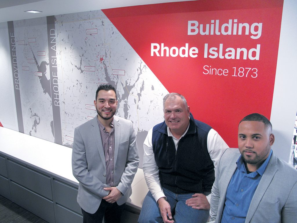 RECOGNIZING OPPORTUNITY: Gilbane Building Co. Vice President and Rhode Island business unit leader John Sinnott is flanked by Christopher L. Calderon, left, and Edwin A. Montas at the company's Providence headquarters, where Sinnott oversees much of the local recruitment efforts to better match the company's workforce with the local community.  / PBN PHOTO/MARK S. MURPHY