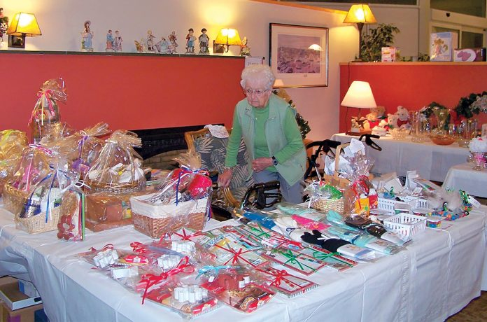 HARVEST FAIR: A woman observes items for sale during last year's Harvest Time Fair, hosted by United Methodist Elder Care, which has since become Aldersbridge Communities. This year's fair will be held Nov. 9-10 at two East Providence locations, Winslow Gardens and Linn Health & Rehabilitation. / COURTESY ALDERSBRIDGE COMMUNITIES