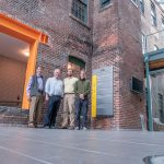 """SECOND WAVE: Initially renovated in 2003, Rising Sun Mills, at 166 Valley St. in Providence, is going through a second wave of renovation for new tenants. Standing in front of the entry area are, from left, H. LeBaron """"Barry"""" Preston, principal, Armory Revival Co.; Robert """"BJ"""" E. Dupré Jr., principal, Armory Revival; Seth Zeren, director of development, Armory Management Co.; and Mark Van Noppen, vice president and managing director, Armory Revival. / PBN PHOTO/MICHAEL SALERNO"""