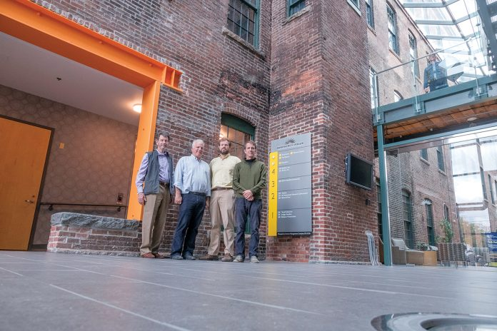 "SECOND WAVE: Initially renovated in 2003, Rising Sun Mills, at 166 Valley St. in Providence, is going through a second wave of renovation for new tenants. Standing in front of the entry area are, from left, H. LeBaron ""Barry"" Preston, principal, Armory Revival Co.; Robert ""BJ"" E. Dupré Jr., principal, Armory Revival; Seth Zeren, director of development, Armory Management Co.; and Mark Van Noppen, vice president and managing director, Armory Revival.