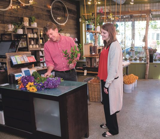COMFORTABLE SURROUNDINGS: Jeffrey Kerkhoff, owner of Jephry Floral Studio on Broadway in Providence, with customer Melissa Lamoine of Cumberland. Kerkhoff said he feels comfortable in a neighborhood that has improved in value and esteem since he first opened his floral business 20 years ago. / PBN PHOTO/MICHAEL SALERNO