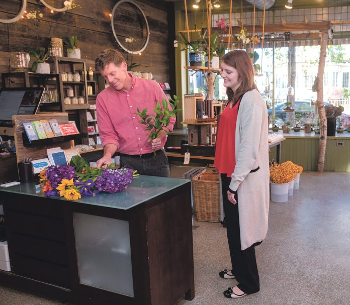 COMFORTABLE SURROUNDINGS: Jeffrey Kerkhoff, owner of Jephry Floral Studio on Broadway in Providence, with customer Melissa Lamoine of Cumberland. Kerkhoff said he feels comfortable in a neighborhood that has improved in value and esteem since he first opened his floral business 20 years ago.