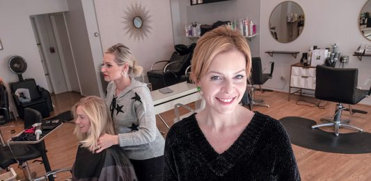 CREATIVE STYLISTS: Leah Carlson, right, is a master stylist/colorist and the owner of La La Luxe salon, with locations in Providence and Warren. In the background is Jenna Frerichs of Providence having her hair styled by Tara McCabe.