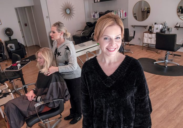 CREATIVE STYLISTS: Leah Carlson, right, is a master stylist/colorist and the owner of La La Luxe salon, with locations in Providence and Warren. In the background is Jenna Frerichs of Providence having her hair styled by Tara McCabe. / PBN PHOTO/MICHAEL SALERNO