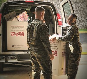 UNLOADING GIFTS: A pair of marines from a base in Quantico, Va., are pictured earlier this year unloading a truck of gifts bound for a local Toys for Tots campaign. / COURTESY MARINE TOYS FOR TOTS FOUNDATION