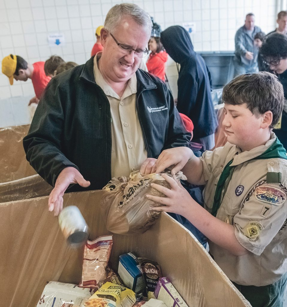 SORTING DONATIONS: Connor Sunderland, a member of Troop 7 Buttonwoods, helps sort food, collected as part of the statewide Scouting for Food Drive, with Narragansett Council of Boy Scouts of America CEO Tim McCandless at the Rhode Island Community Food Bank in Providence. / PBN PHOTO/MICHAEL SALERNO