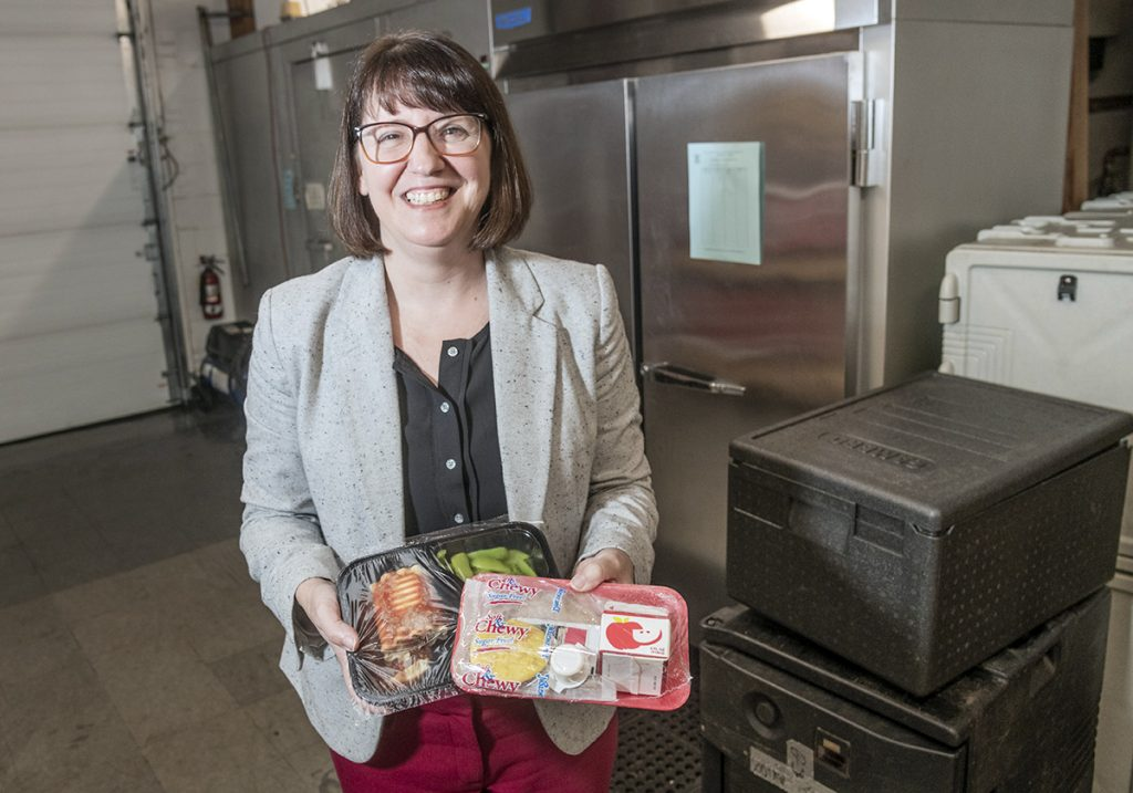 DELIVERED MEALS: Heather Amaral, executive director of Meals on Wheels of Rhode Island, holds samples of the organization's packaged meals, which are delivered to the elderly and homebound throughout the state.  / PBN PHOTO/MICHAEL SALERNO